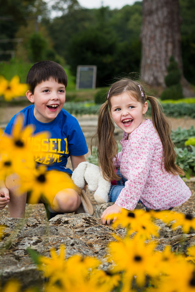 Laughing in the flowers, children's portraiture by Sarah Hart Photography, Ightham Mote, Kent