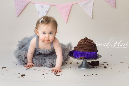mucky hands and face, 1st birthday cake smash session, at Sarah Hart Photography studio, chocolate cake face