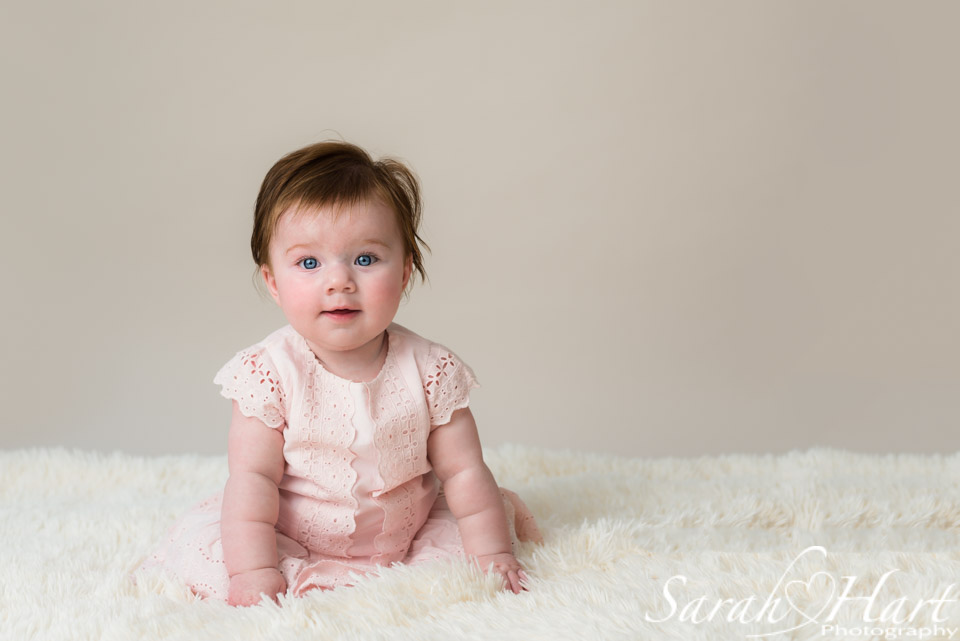 Sitting up unaided, gorgeous baby photo, neutral backdrop, baby blues, Sarah Hart image