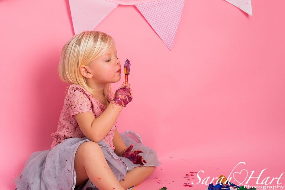 girl painting her nose at her cake smash disaster