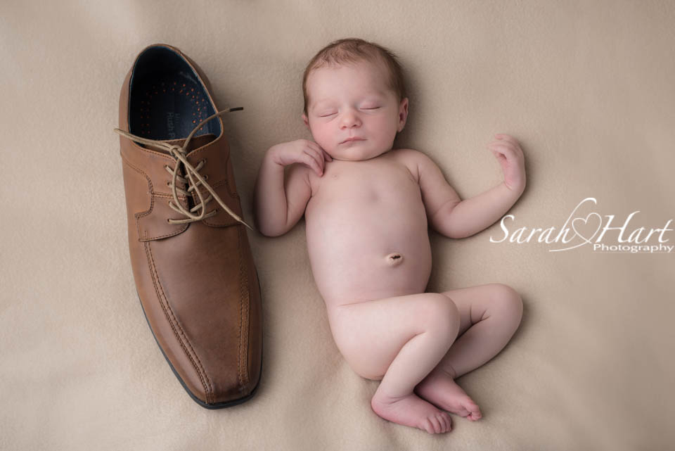 Newborn next to daddys shoe unusual baby photograph baby photo shoot in tonbridge