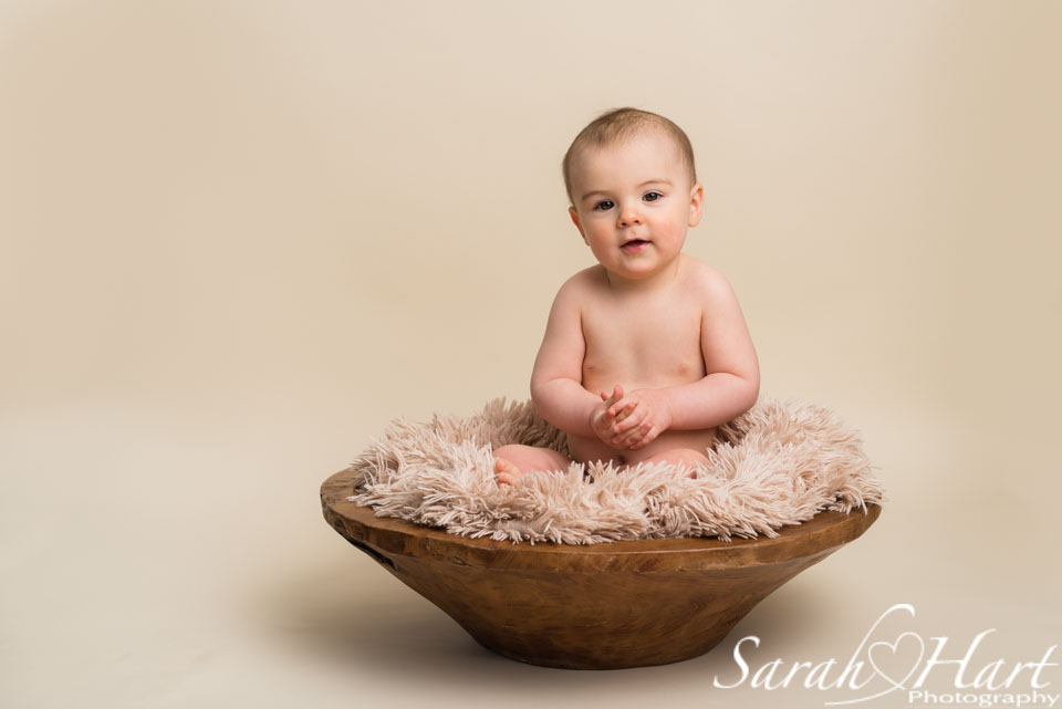 baby in a wooden bowl, inquisitive baby expressions, studio photography in tonbridge