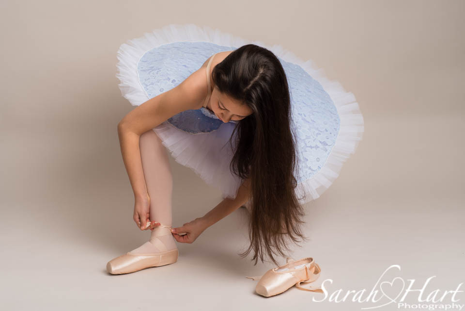 preparing to dance, ballerina putting on her ballet shoes