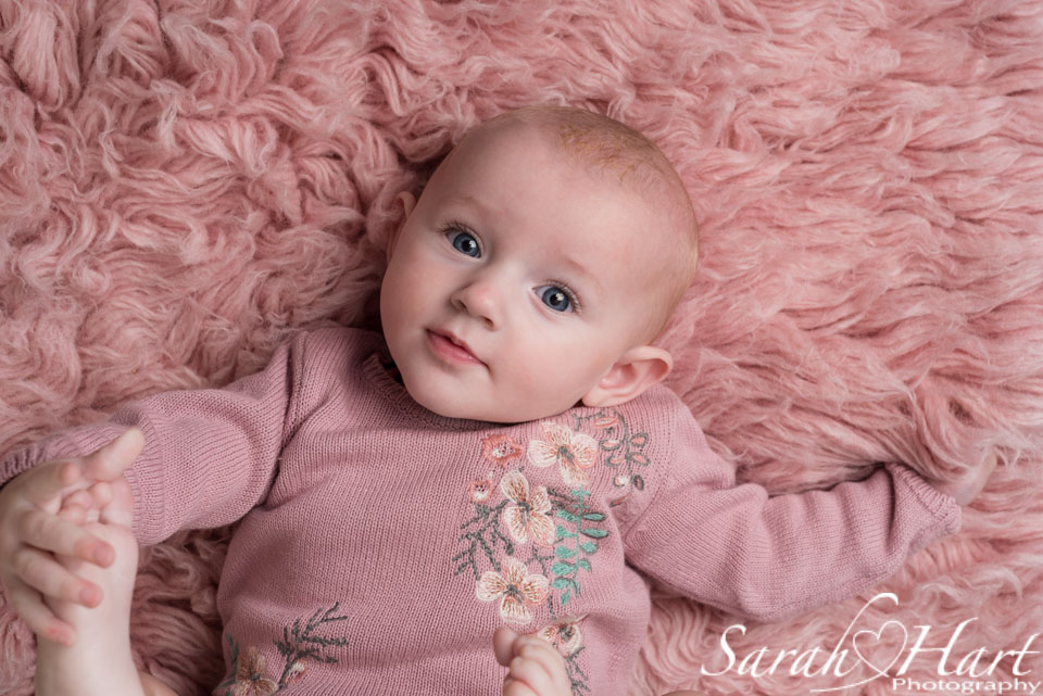 intense stare from baby, pink fur flokati, big blue eyes, Crowborough photographer