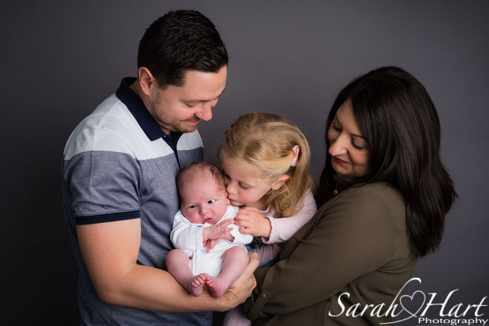 A kiss for her baby brother, family photoshoot with newborn, maidstone photographer