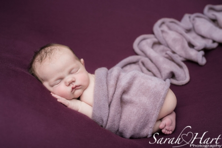 Newborn tummy pose, deep pink wrap and purple backdrop, baby pictures in maidstone
