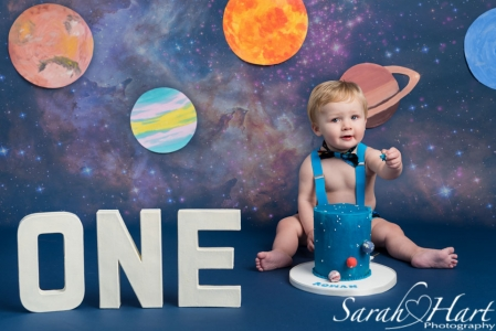 Outer space themed cake smash, sharing cake, navy backdrop, Hildenborough photographer