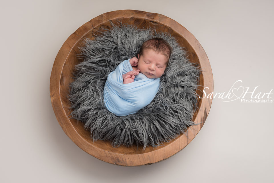 baby in a wooden bowl with grey fur and blue wrap, Tonbridge baby photographer