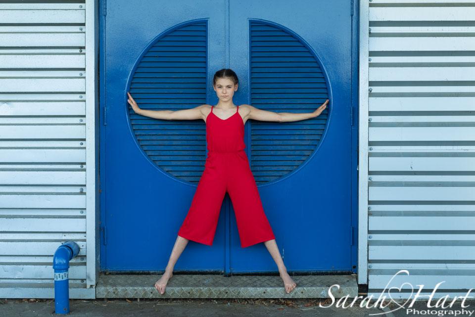striking dancer in red against blue door, tunbridge wells portrait photographer