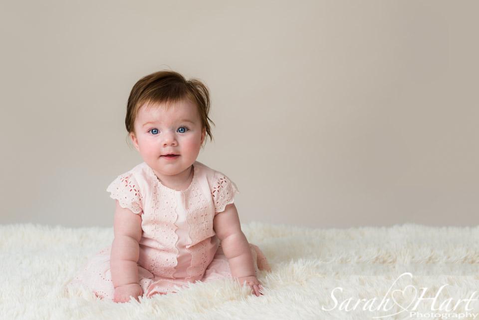 Sitting up unaided, gorgeous baby photo, neutral backdrop, baby blues, Sarah Hart image