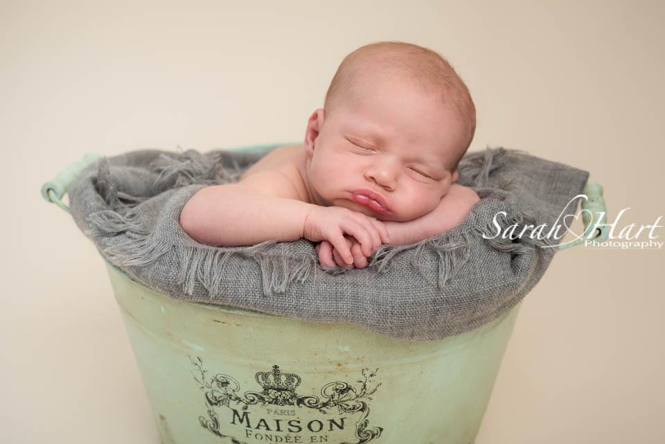 baby in a green bucket, tunbridge wells photographer, experienced baby photographer kent