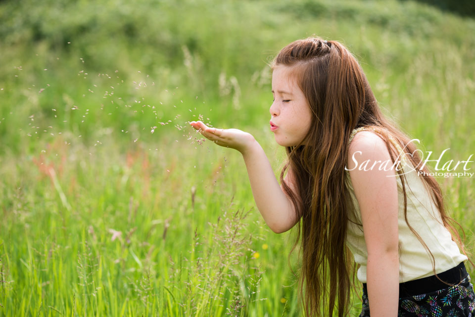 Blowing grass seeds, girl in meadow, Kent photographer, Sarah Hart Photography, Maidstone, Tonbridge