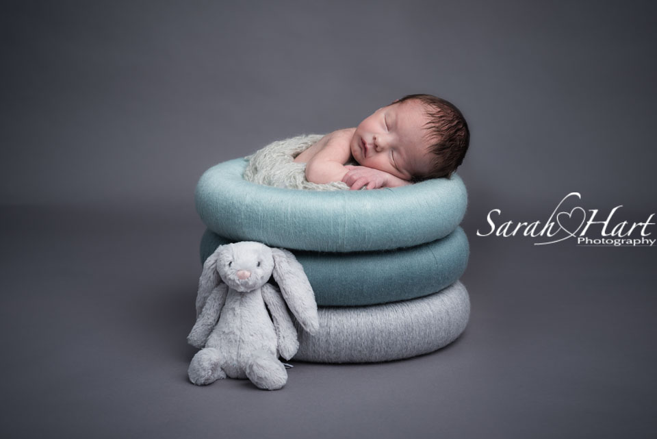 Newborn baby in posing rings, teals and greys, with little bunny, Kent baby photographer