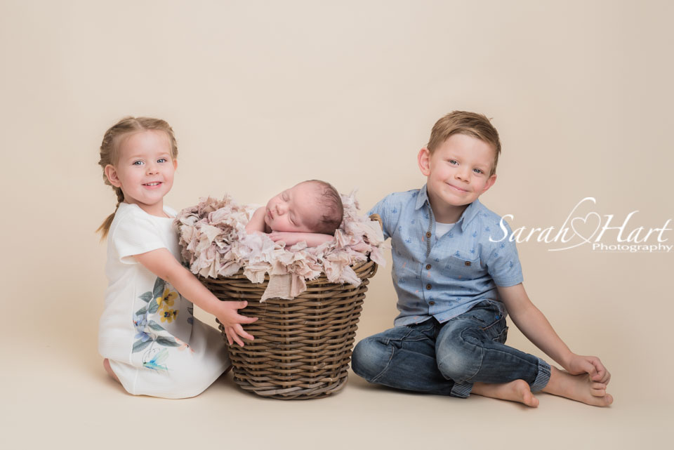 Newborn baby with her brother and sister, composite image, safety first