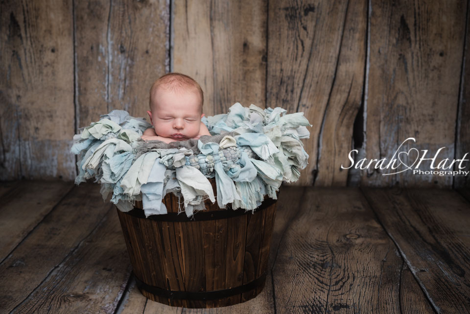 Newborn in wooden prop with blue ruffle rug, Hildenborough newborn photographer
