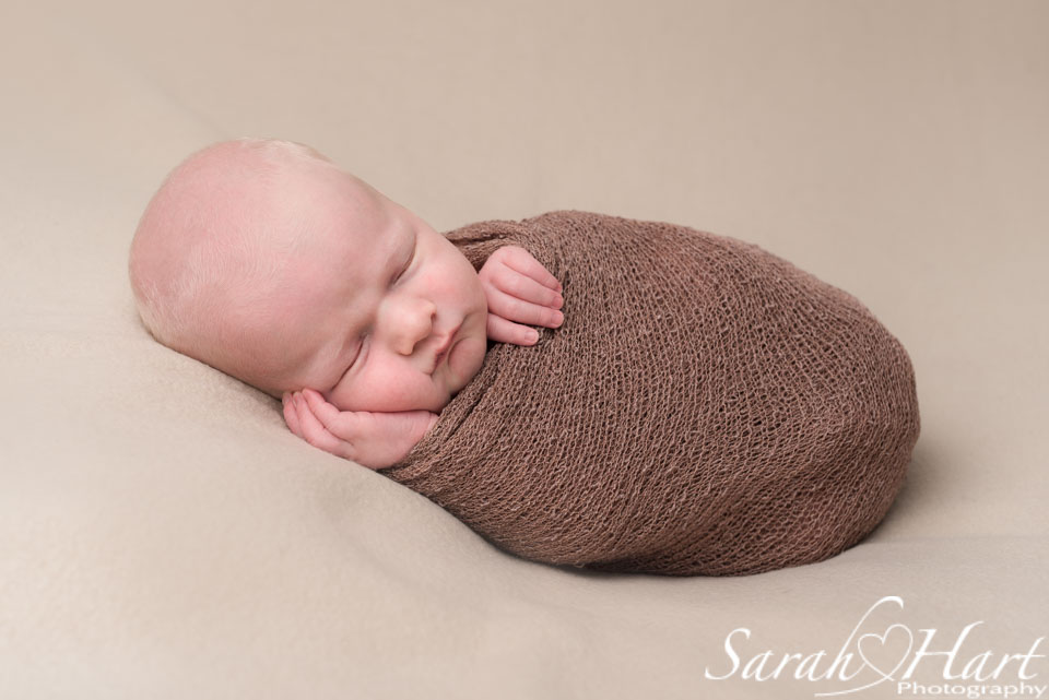 Baby photos in tonbridge, kent, blonde haired baby, wrapped up snug