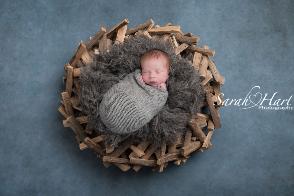 newborn snug on grey fur with driftwood garland, tonbridge studio photographer