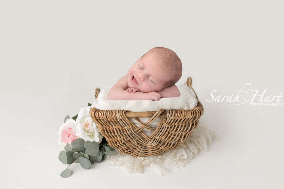 smiley newborn in basket with flowers, southborough photographer