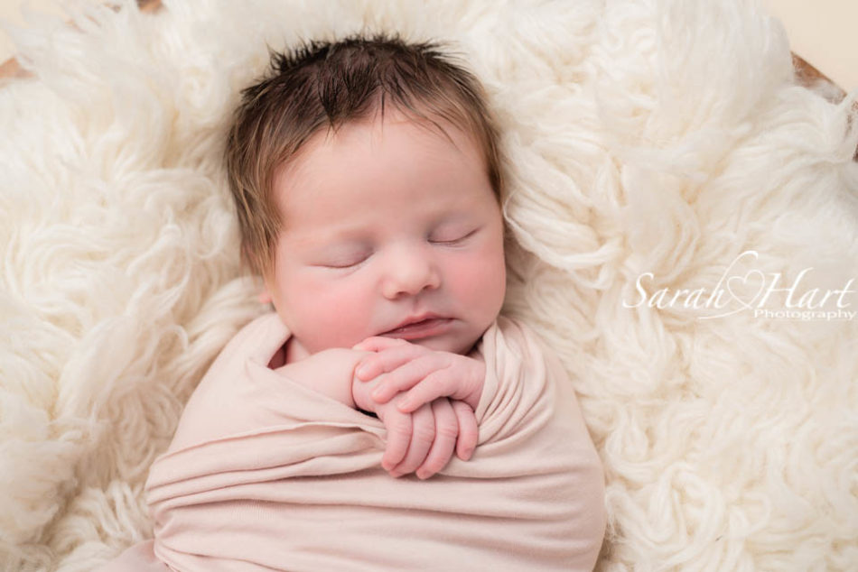 newborn baby girl in pale blush pink wrap, sevenoaks baby photographer