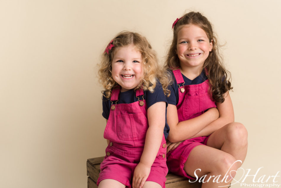 image of sisters grinning together, tonbridge portrait photographer