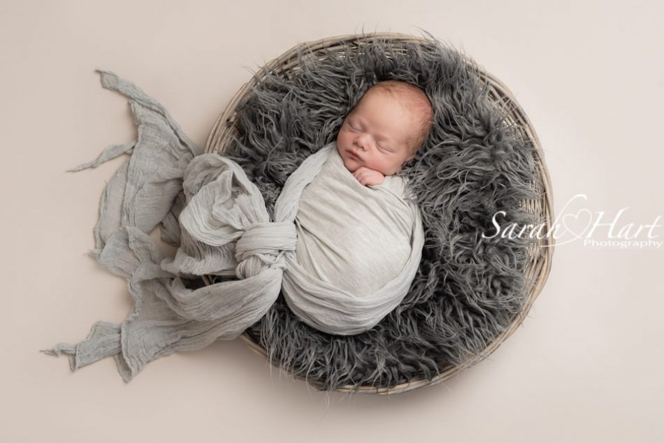 newborn wrapped in a grey swaddle, artistry of a newborn photographer, kent