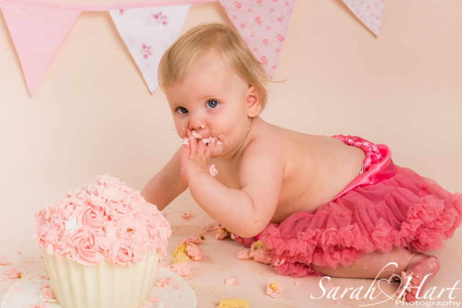 baby girl eating cake at her birthday cake smash session, sevenoaks