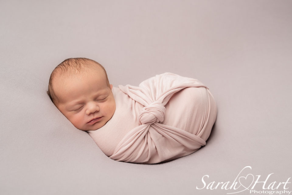 newborn session tunbridge wells, baby swaddled in pink wrap