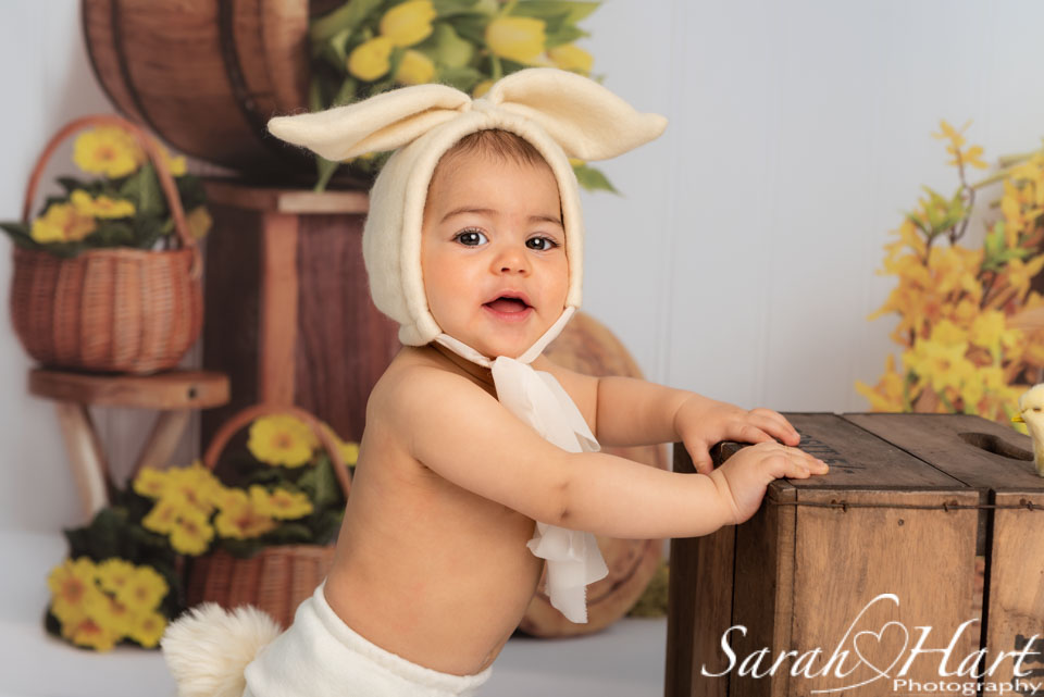 baby girl in bunny outfit stood at crate, mini session photography in kent