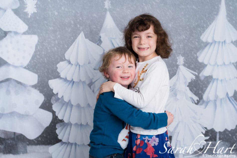siblings hugging at a Chrsitmas themed photo shoot, Tunbridge Wells
