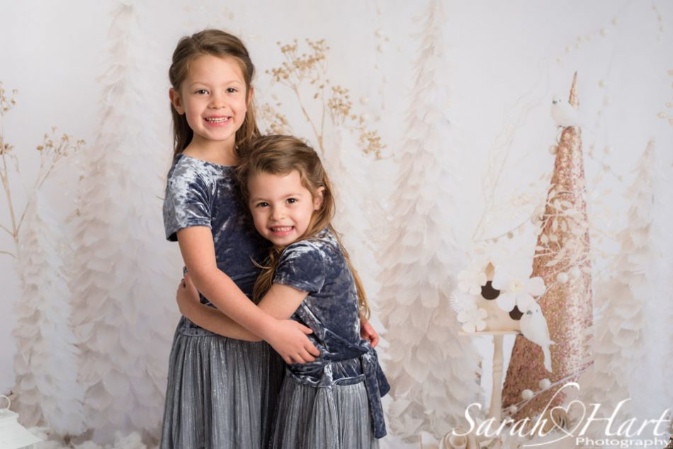 Two sister hugging on Xmas themed backdrop