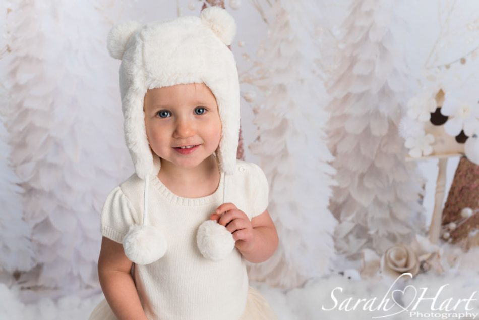 little girl with teddy bear hat with Christmas backdrop behind her