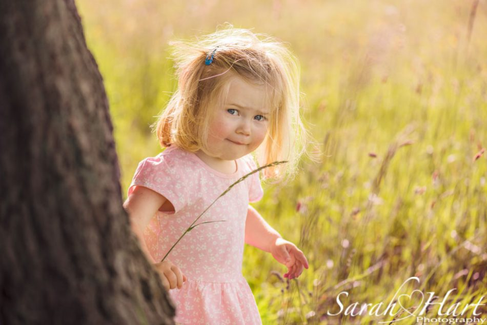 peeking round a tree on at her family photographer, Kent