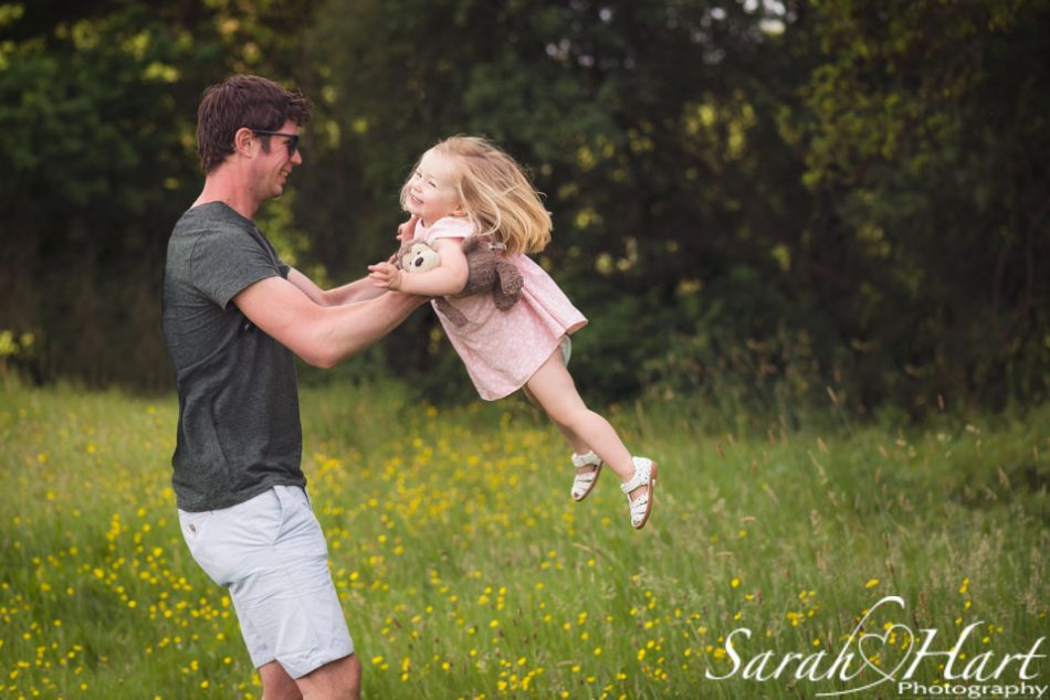 daddy swinging daughter around on family photoshoot near tonbridge