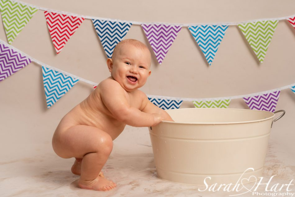 Boy splashing around at his cake smash tub time, Kent photographer