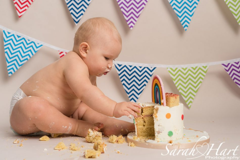 Baby boy enjoying his rainbow cake smash photography session in Tonbridge, Kent