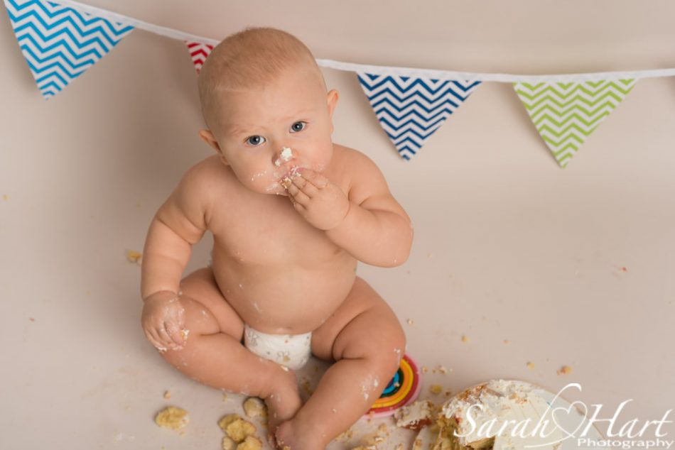 Boy enjoying his rainbow theme cake smash, Kent photographer