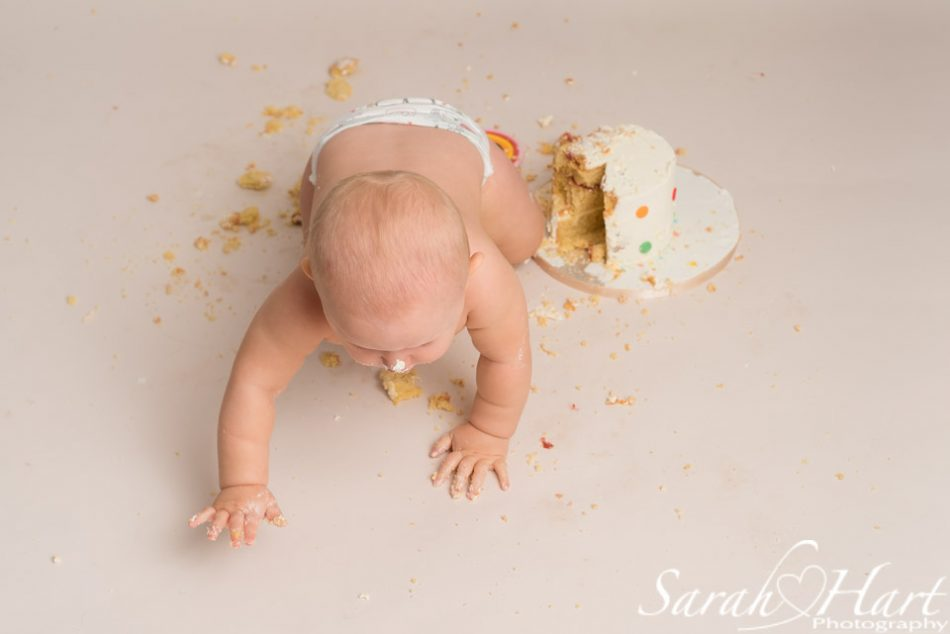 Boy crawling away from his cake smash!
