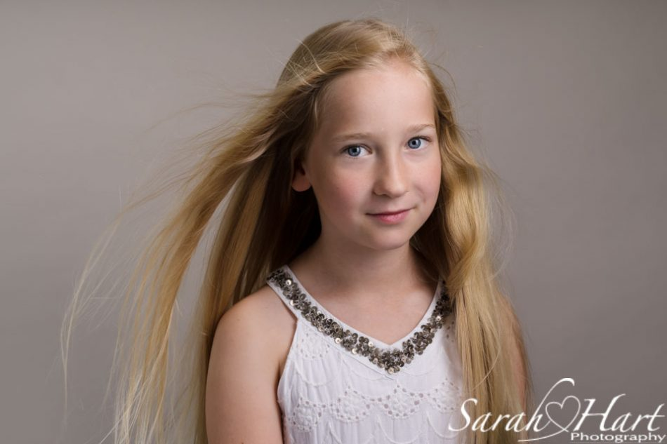 headshot of girl with hair being blown, Kent portrait photographer