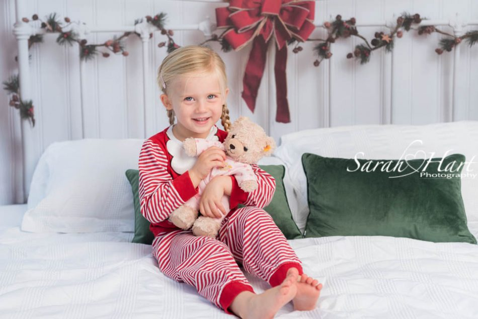 Girl cuddling teddy on a bed Christmas sessions