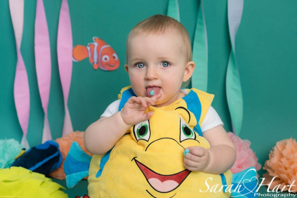 little girl sticking her tongue out at her cake smash photo shoot, Edenbridge photographer