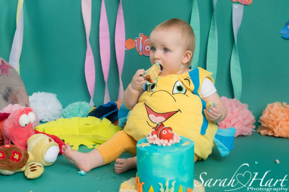 little girl eating her first taste of cake, under the sea cake smash, kent photography