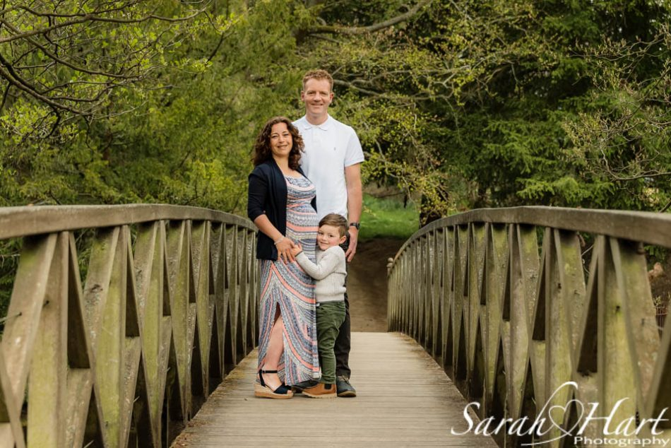 A family of three for bump photos stood on bridge