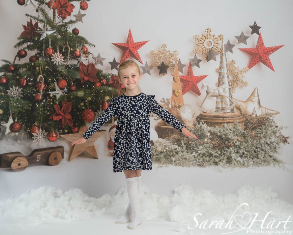 Young girl at Xmas themed photoshoot with snow on ground