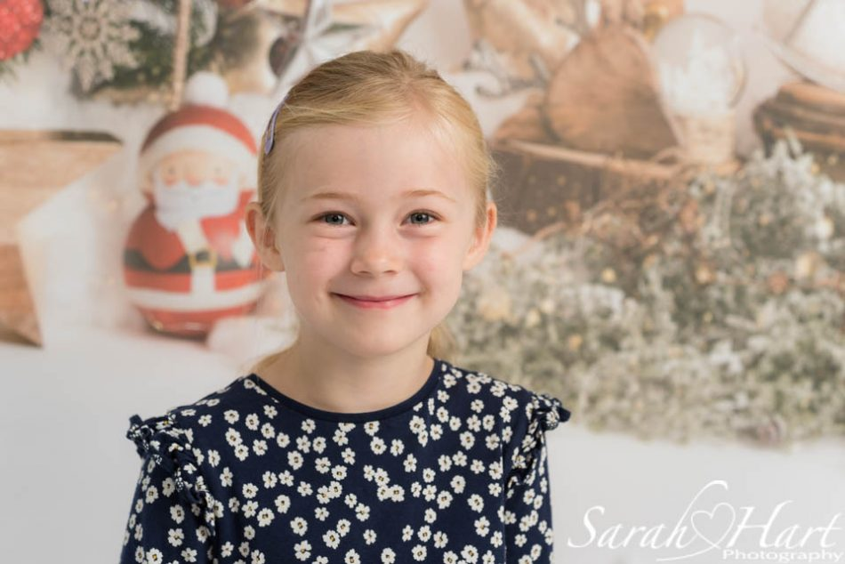 Young girl with mini Father Christmas behind her